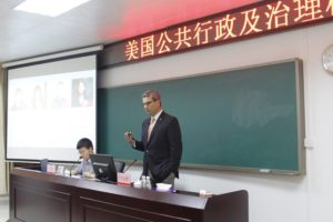 Zerunyan lectures at the Bao'an District Party School, describing research and a student project for the UN. Price Ph.D. student Bo Wen, left, translates.