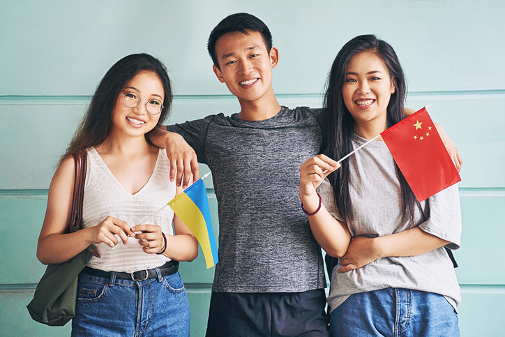 Group of three happy international chinese asian students smiling and holding flags of China and Ukraine in university